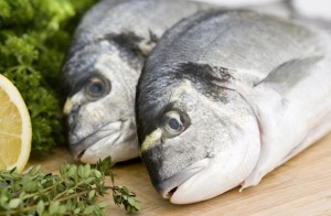 Two fresh sea bream on wooden board with herbs and lemon