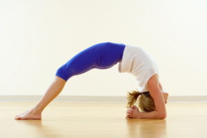 Studio shot of woman in headstand bridge yoga pose