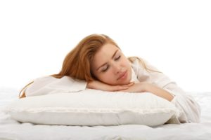 Young beautiful girl sleeps in the bed hugging a pillow on his stomach. Healthy sleep. Isolated on white background.