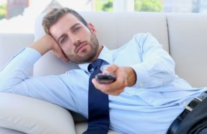 stock-footage-businessman-sitting-on-couch-watching-tv-in-the-office-620x400